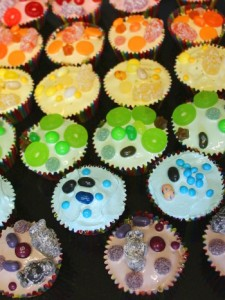 Cupcakes in rainbow-striped cases. Each row of cupcakes is iced in a colour. From front to back: purple, blue, green, yellow, orange and red. An assortment of matching coloured sweets is on each one.